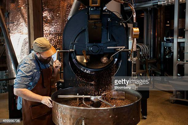 Coffee roaster Joshua Read empties freshly roasted Sumatran peaberry coffee beans from the smallbatch roaster at the Starbucks Corp Reserve Roastery...