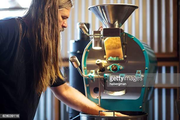 Coffee Roaster Running Hands Through Beans