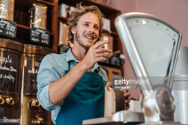 Coffee roaster weighing coffee in his shop