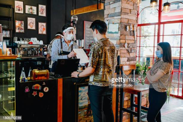 coffee shop barista with face masks, lockdown, quarantine, coronavirus, back to normal concept - lining up stock pictures, royalty-free photos & images