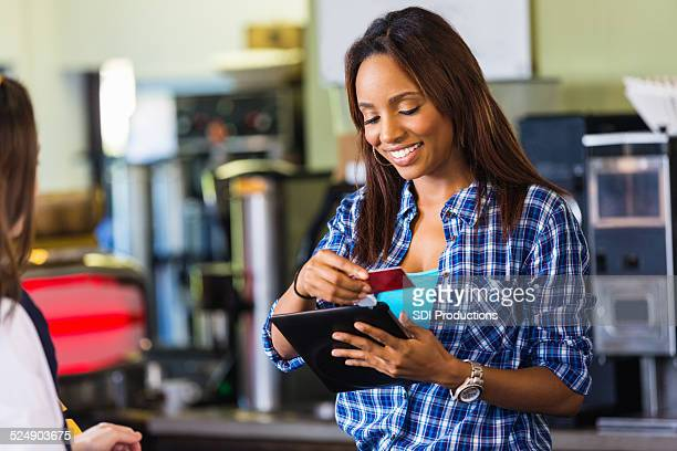 Coffee shop cashier swiping card on digital tablet reader