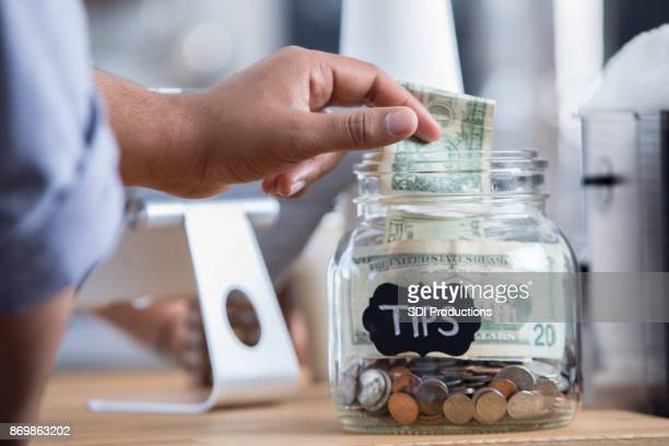 coffee shop customer places cash in a tip jar - jar stock pictures, royalty-free photos & images