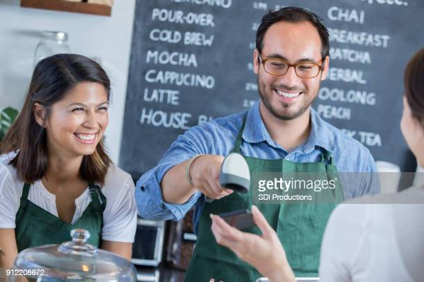Coffee shop customer uses smart phone to pay for purchase