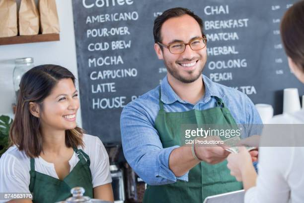 Coffee shop employee accepts payment from customer