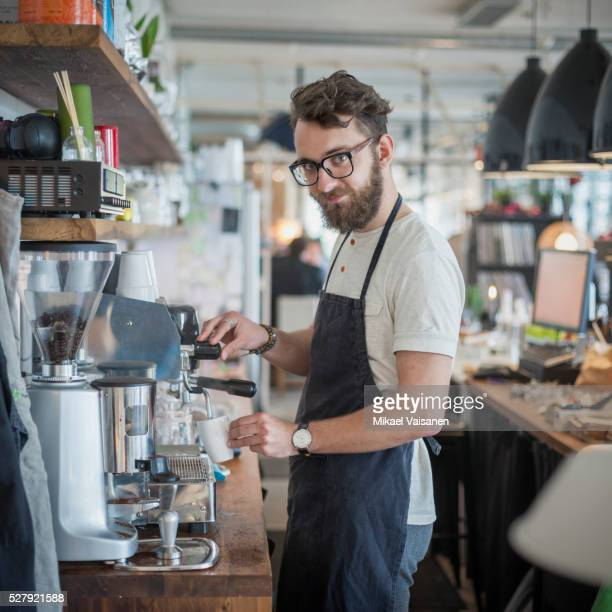 coffee shop owner behind counter making espresso