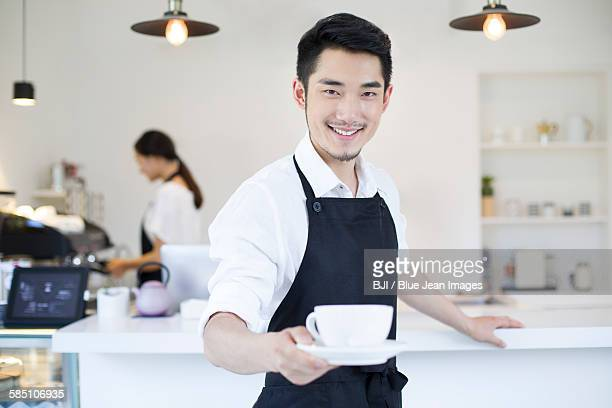 Coffee shop owner holding a cup of coffee
