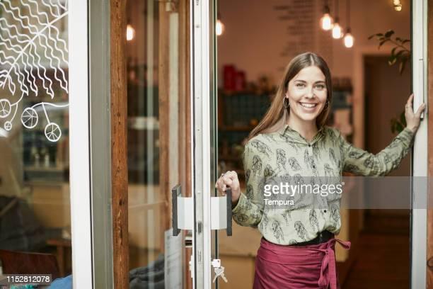kaffeehausbesitzer halten die tür offen und schauen auf kamera. porträt mit kopierplatz. - tür öffnen stock-fotos und bilder