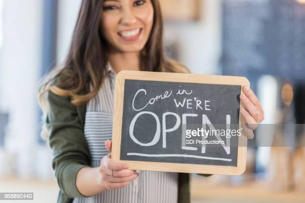 Coffee shop owner holds 'OPEN' sign