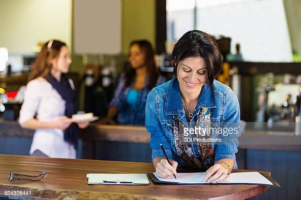 Coffee shop owner reviewing spreadsheets