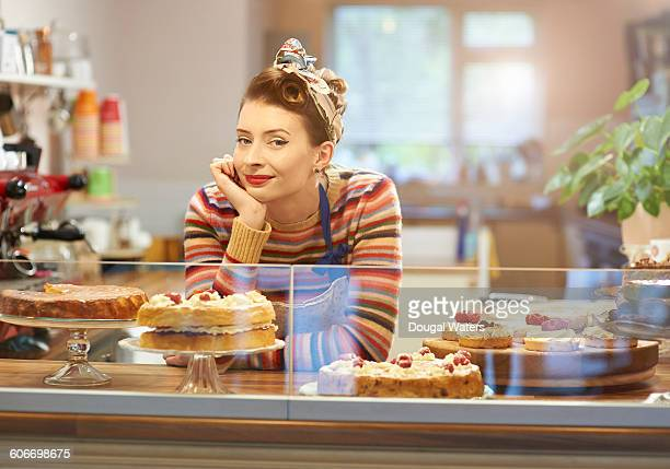 Coffee shop owner standing behind cake counter.