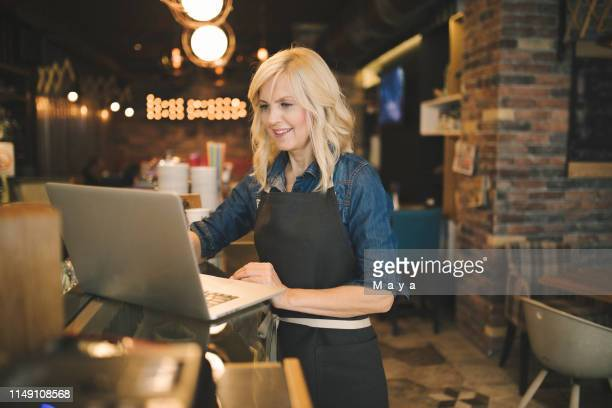 coffee shop owner working on laptop - restaurant manager stock pictures, royalty-free photos & images