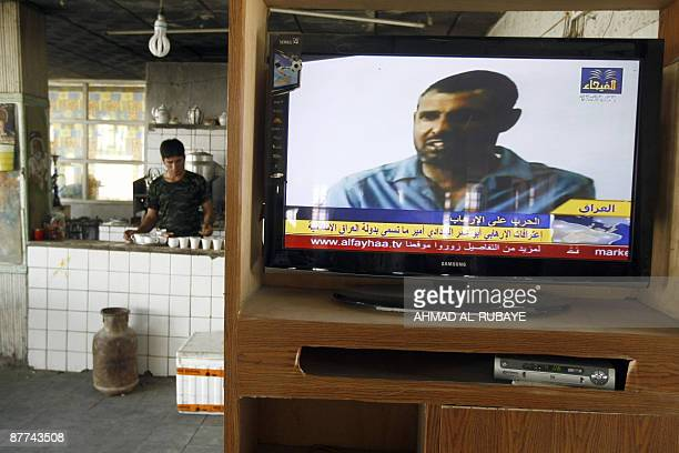 A coffee shop workers lays out cups while a local Iraqi television channel shows the confession of an Iraqi man allegedly Abu Omar alBaghdadi said to...