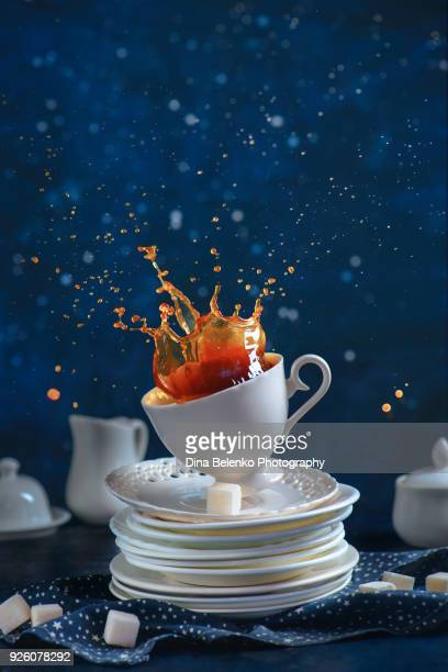 Coffee splash in a vintage porcelain cup on a stack of dishes and tea saucers. Dynamic food photography in motion. Kitchen mess with high-speed liquid motion.