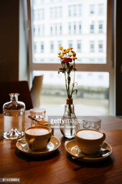 Coffee, water and light bulb vase with flowers on the table