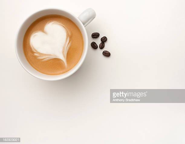 A coffee with a heart shape drawn in its foam
