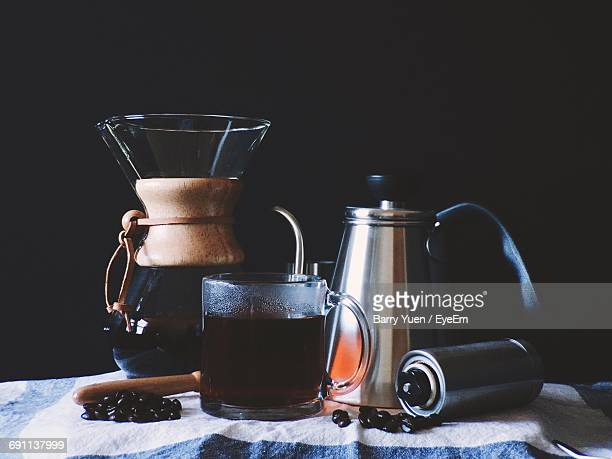 Coffee With Containers On Table Against Black Background