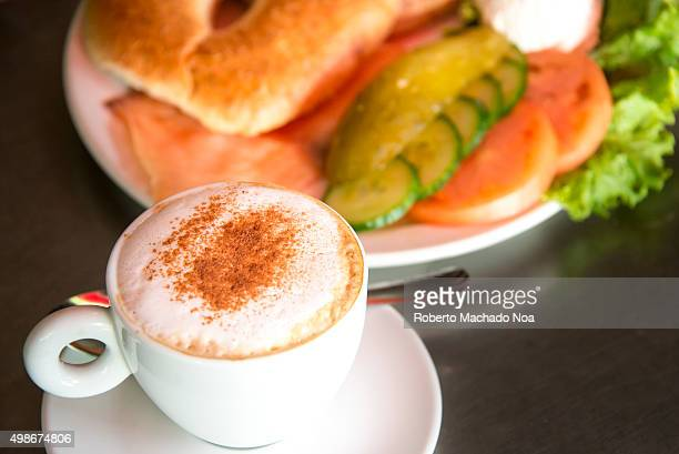 Coffee with doughnut burger Cappuccino with chocolate sprinkled on top placed beside a serving of doughnut burger at a restaurant in Toronto Canada