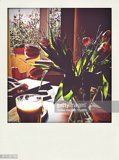 Coffee with flower vase on table at home
