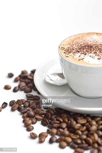 Coffee with foam in a white cup on saucer with coffee beans