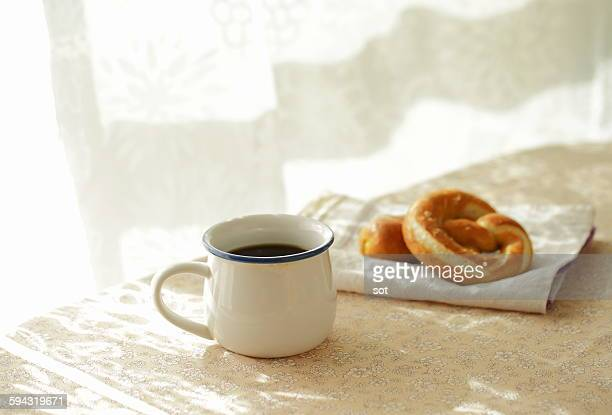 coffee with soft pretzels bread on the table - 朝 ストックフォトと画像