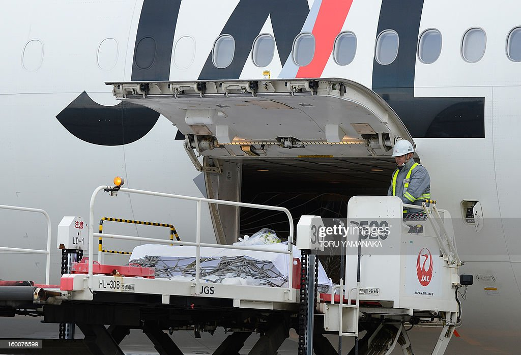 A coffin carrying the last Japanese victim of the Algerian hostage crisis is unloaded onto a cargo palette from a plane at Narita Airport, outside Tokyo on January 26, 2013. The body of the last of 10 Japanese killed in the Algerian hostage crisis arrived in Japan by commercial flight, a day after the bodies of the nine others returned home with seven Japanese survivors. AFP PHOTO / Toru YAMANAKA
