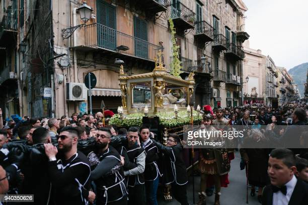 A coffin containing a figure of Jesus passes through the streets of Palermo followed by Christian believers On the holy Friday before Easter many...