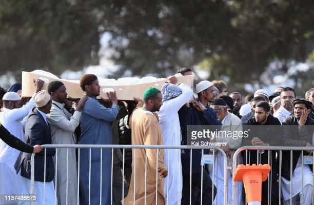 Coffin containing the body of a victim of the Christchurch mosque attacks is carried during a mass burial at Memorial Park Cemetery on March 22, 2019...