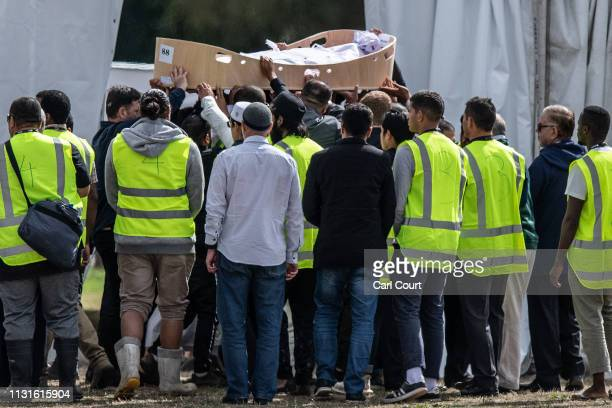 A coffin containing the body of a victim of the Christchurch terrorist attack is carried for burial at Memorial Park Cemetery on March 20 2019 in...