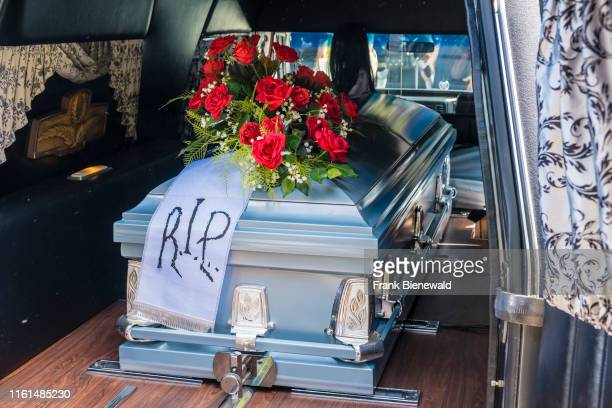 Coffin, decorated with red roses, inside of a hearse.
