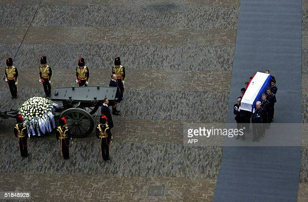 A coffin draped with the Dutch national flag carrying the remains of Prince Bernhard is taken into the church Nieuwe Kerk in Delft 11 December 2004 A...