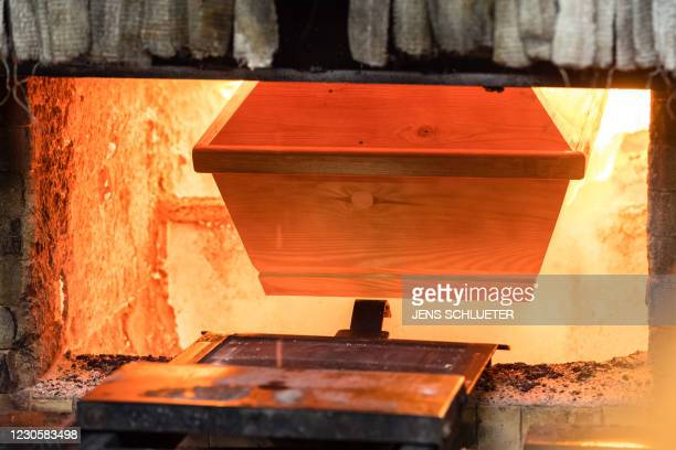 Coffin is moved for cremation into the furnace at the crematorium in Meissen, eastern Germany on January 13 during the ongoing novel coronavirus...