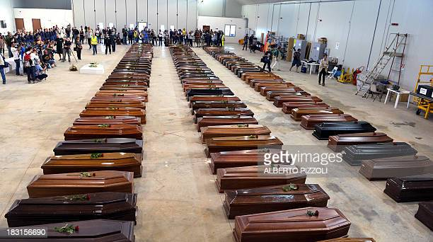 Coffin of victims are seen in an hangar of Lampedusa airport on October 5, 2013 after a boat with migrants sank killing more than hundred people....
