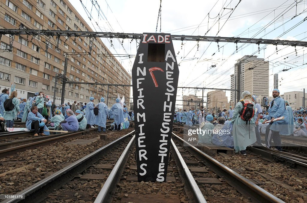 A coffin stands on tracks set by French anaesthetist nurses sitting near the Montparnasse train station on May 18, 2010 in Paris, during a demonstration blocking the speed train (TGV) traffic, to protest against their work conditions.
