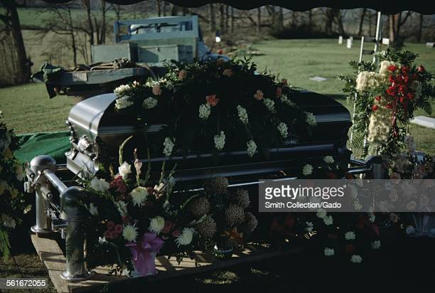 Coffin with flowers, in the shade under a tent, a pickup truck in the background, in a graveyard during a funeral, 1965.