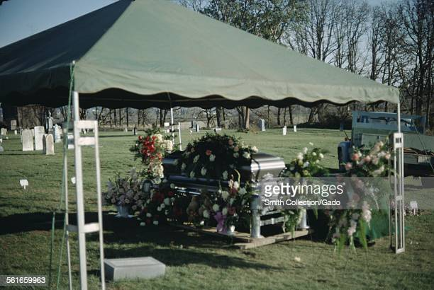 Coffin with flowers, under a tent in a graveyard during a funeral, a Chevrolet pickup truck in the background, 1965.