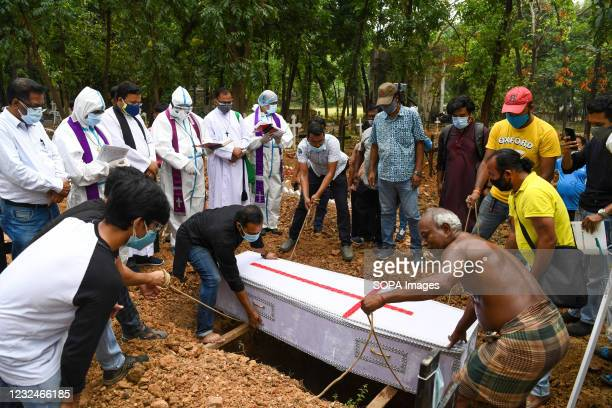 Coffin with the covid 19 deceased man being put down into the grave, during a burial by Bangladeshi Christians at a cemetery.
