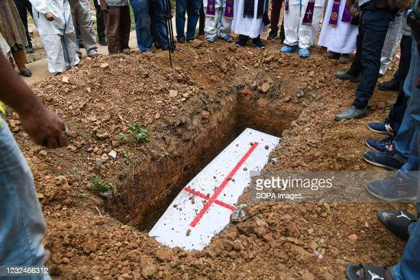 Coffin with the covid 19 deceased man seen in the grave during a burial by Bangladeshi Christians at a cemetery.