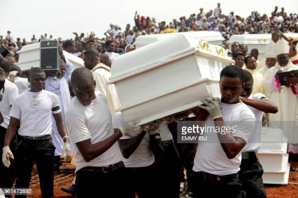 Coffins are carried during a funeral service for 17 worshippers and two priests who were allegedly killed by Fulani herdsmen at AyatiIkpayongo in...