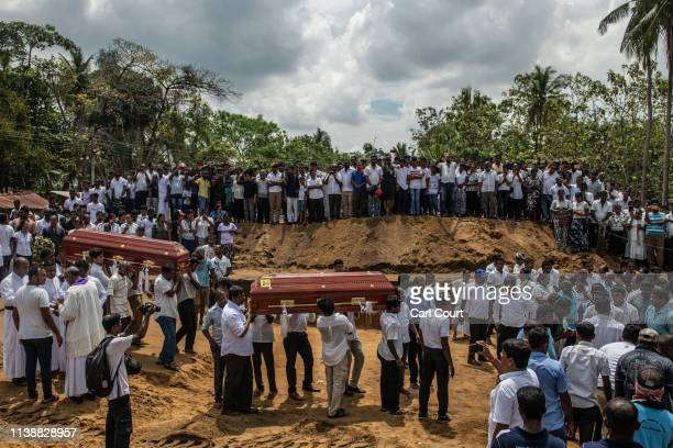 Coffins are carried to a grave during a mass funeral at St Sebastian's Church on April 23 2019 in Negombo Sri Lanka At least 311 people were killed...