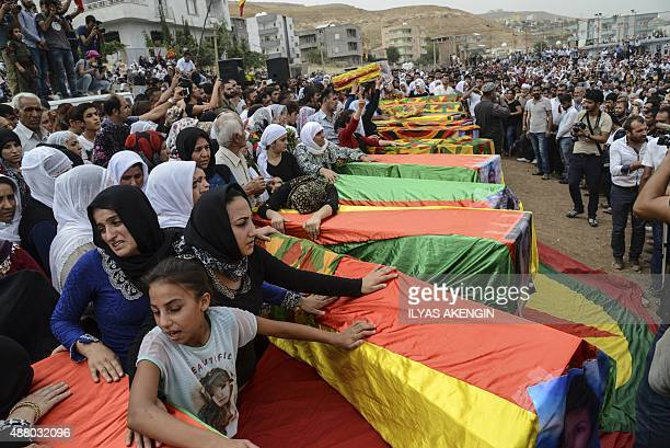 Coffins are draped in the Kurdish flag as mourners gather for the funerals of people killed during clashes between Turkish forces and militants of...