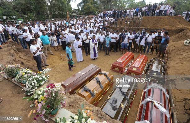 Coffins are laid for burial as a Sri Lankan catholic priest surrounded by devotees and family members of the victims carry out religious rituals...