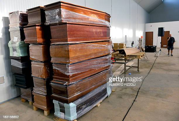 Coffins are picture in a hangar at the Lampedusa airport on October 5, 2013 after a boat with migrants sank killing more than hundred people. Italy...