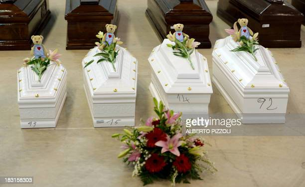 Coffins of children are pictured among Coffins of victims in an hangar of Lampedusa airport on October 5, 2013 after a boat with migrants sank...