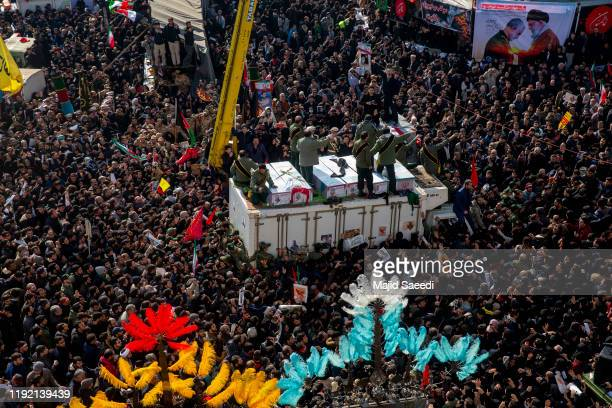 Coffins of Iranian Major General Qassem Soleimani and others who were killed in Iraq by a US drone strike are carried on a truck surrounded by...