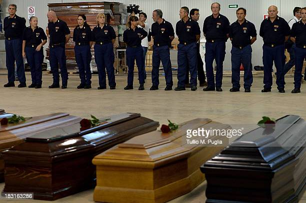 Coffins of some of the African migrants killed in a shipwreck off the Italian coast sit in a hangar at the Lampedusa airport on October 5, 2013 in...
