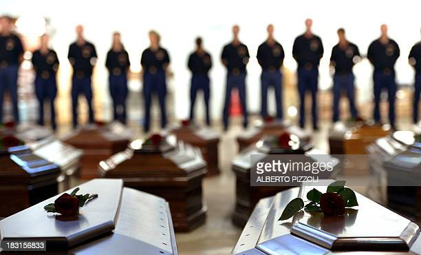 Coffins of victims are seen in an hangar of Lampedusa airport on October 5, 2013 after a boat with migrants sank killing more than hundred people....
