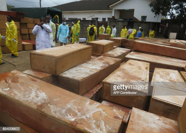 Coffins with the remains of the victims of a mudslide are prepared to be carried to the cemetery on trucks draped with the Sierra Leone flag in...