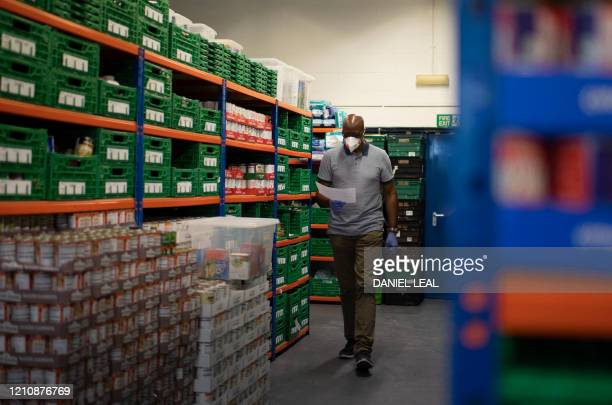 Cofounder and Chair of the First Love foundation foodbank Aerold Bentley walks past goods for distribution to families at the First Love foundation...