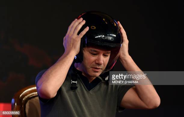 Cofounder and Chief Executive Officer of US tranportation company Uber Travis Kalanick wears a helmet as he speaks at an event in New Delhi on...