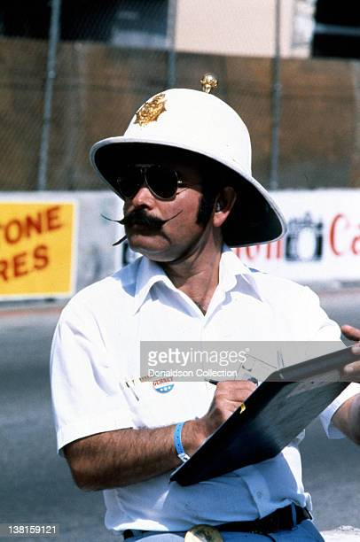 Cofounder Dan Gurney takes notes as celebrities race cars on the streets during the Long Beach Grand Prix in 1979 in Long Beach California